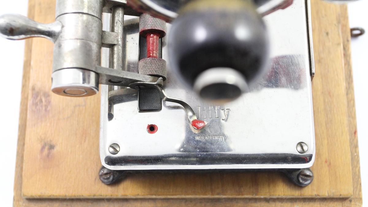 Trolig et stempel, hvor ulike symboler og tall kan trykkes ved å snurre rundt på skiven. Har blitt brukt på bankkontor.  Det hører til en hette av tre med hank som passer over gjenstanden og passer i fordypningen på treplaten i bunnen av gjenstanden. Lokket har kroker som hektes i øyeskruene på bunnplatens sider. Lokket er ikke fotografert.