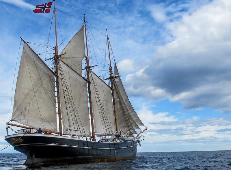 """Skonnerten """"Svanen"""" med tre master og for fulle seil ute på vannet, med norsk flagg, sett fra styrbord."""