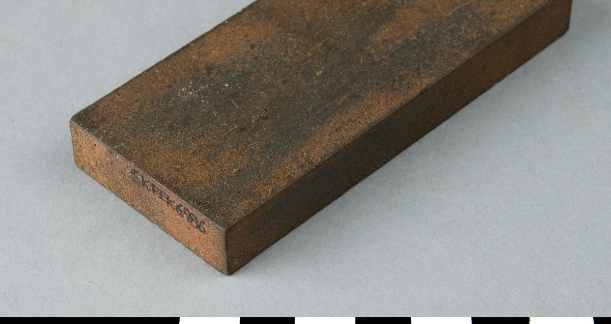 Bryne i rektangulär form. Brynet i rödbrun rostliknande färg är tillverkat i ett konstmaterial, som kan vara kiselkarbid eller aluminiumoxid. I ena änden av brynet är stämplat 24 M.