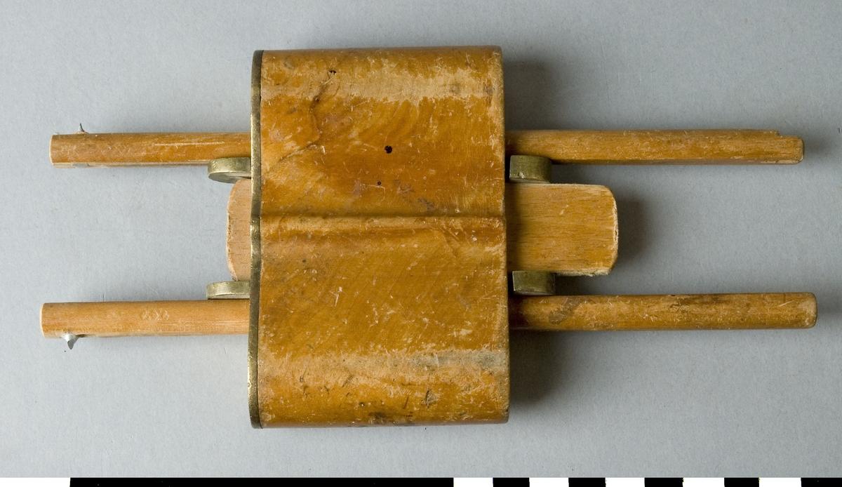 Strykmått av trä. Strykmåttet består av en klots av björk genom vilken två pinnar av björk löper. I samma riktning mellan pinnarna löper en skjutbar kil för låsning av pinnarna för rätt mått. I ena änden av varje pinne sitter ett stift av stål för påritning av mått på arbetsstycke. Klotsen utgör anslaget. Mellan kilen och varje pinne sitter en genomgående mässingsskena. Klotsens anslagssida har ett mässingsbeslag.  Funktion: Ritsa avståndsmått på arbetsstycken, inställningsbar