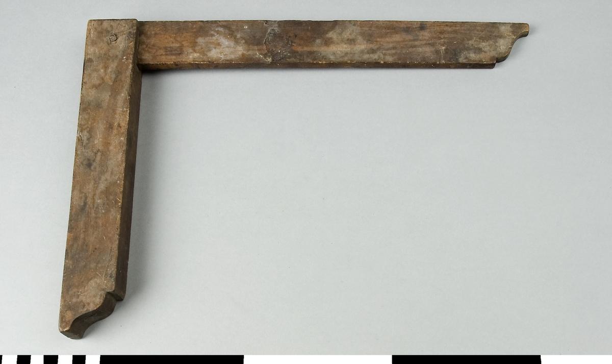 Vinkelhake av trä. Ändarna på anslag och vinkel är figursågade för dekorationens skull. Vinkelhaken är mörk i träet och har flera fläckar.  Funktion: Markering av 90º vinkel på arbetsstycke