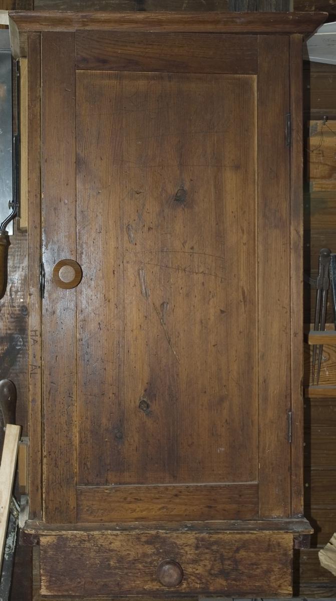 Skåp av trä för förvaring av verktyg. Verktygsskåpet är brunbetsat med en dörr som är tillverkad med ram och fyllning. Dörren har en rundsvarvad knopp. För låsning med hänglås finns låsöglor monterade på skåpet. Överstycket på skåpet är överskjutande med grofilerade lister på sidorna och framsidan. Profillist finns på bottenstycket. I skåp och dörr finns inredning för verktyg. I mitten högst upp på bakstycket finns en upphängningsögla. På insidan av skåpdörren sitter en lapp med handskriven förteckning över verktyg. På insidan sitter dessutom en urklippt tidningsbild av en racerbil av experimentmodell kallad SILVER BULLET från England. På bakstyckets insida sitter ett schema från Tekniska aftonskolan i Stockholm arbetsåret 1817-1918. Till skåpet hör också en utdragslåda, märkt b, med svarvad knopp. En ståltråd med diametern 4 mm, 220 mm långt, som i ändarna bockats till krokar medföljer skåpet. Lådmått: B= 425 mm, Dj= 203 mm, H= 104 mm.  Funktion: Förvaring av verktyg