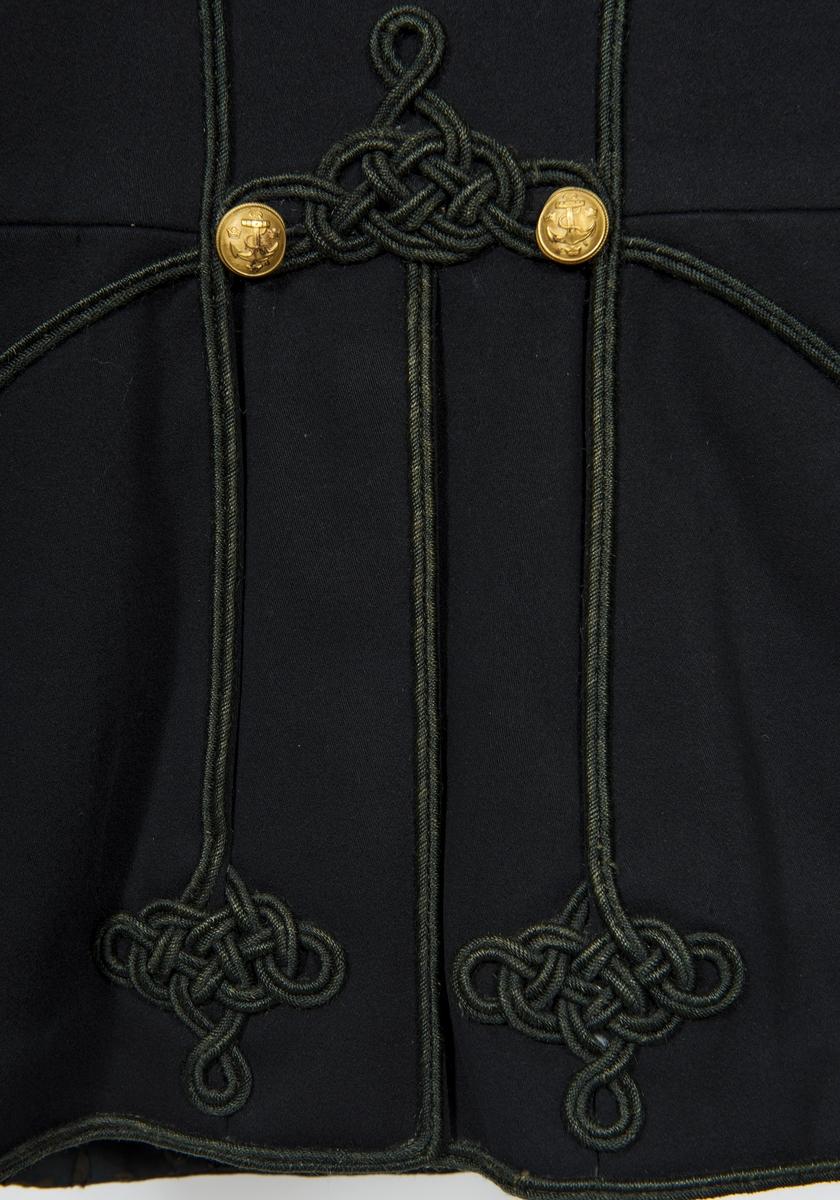 Attila av blått kläde med svart snörmakeri fodrad med svart satin, stickad. 3 rader knappar om 10 st i varje, de i mitten halvsferiska, samtliga förgyllda ankarknappar med 3 kronor. I ryggen två ankarknappar. Axelklaffar av svart silkesträns med förgyllt granatmärke. 2 små innerfickor.