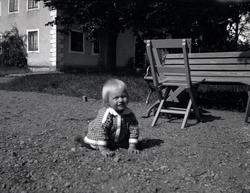 Ett barn som kryper på Tuna gård.