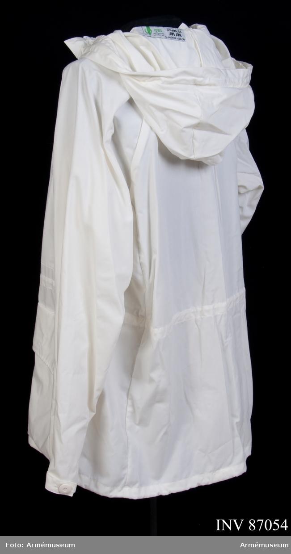 """Snöblus i vitt tyg. Något tunnare tyg än den andra modellen. Etikett i nacken: """"M 7379-304000-0, 1992, Valtion Pukutehdas, Finland, Försök 92-93, att passa kroppssmått 190 cm 75 kg""""."""