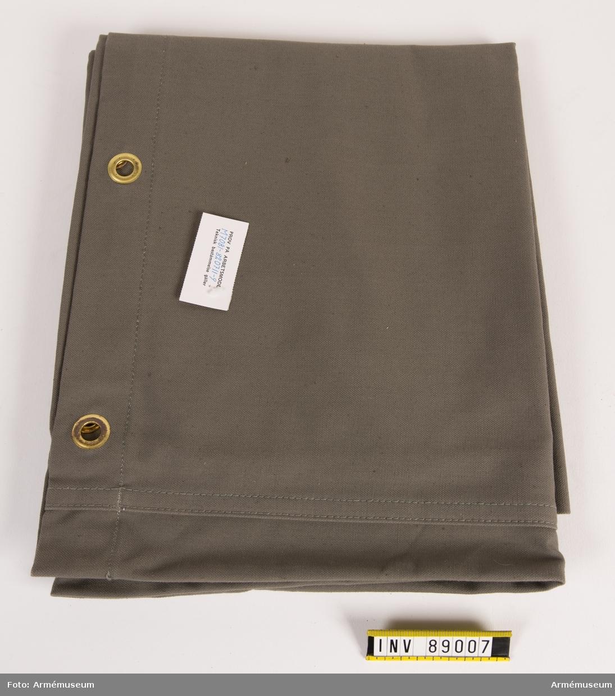 """Packsäck med öljetter i metall. Vidhängande lapp med text: """"Prov på arbetsmodell M 7081-820711-9 Teknisk bestämmelse gäller""""."""