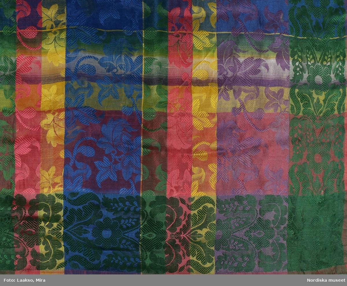 Kvadratiskt halskläde av sidensatin, rutigt i starka färger blått, grönt, gult rosa och lila. Över rutningen ett invävt tätt växtmönster med kantbårder som på 2 sidor har mönstret i grönt och på 2 i gult. Upprispad frans runtom.  i mycket gott skick. Liknar i typ 87595 från Östra hd i Blekinge. Typen kallas Barcelonadukar och togs hem av sjömän från Barcelona. Även i svenska sidenväverier finns anteckningar om barcelonadukar så troligen togs de upp även här./ Uppgifter från Elna Mygdal: Amagerdragter, Kphmn 1930 sid 10, not /Berit Eldvik 2011-11-24