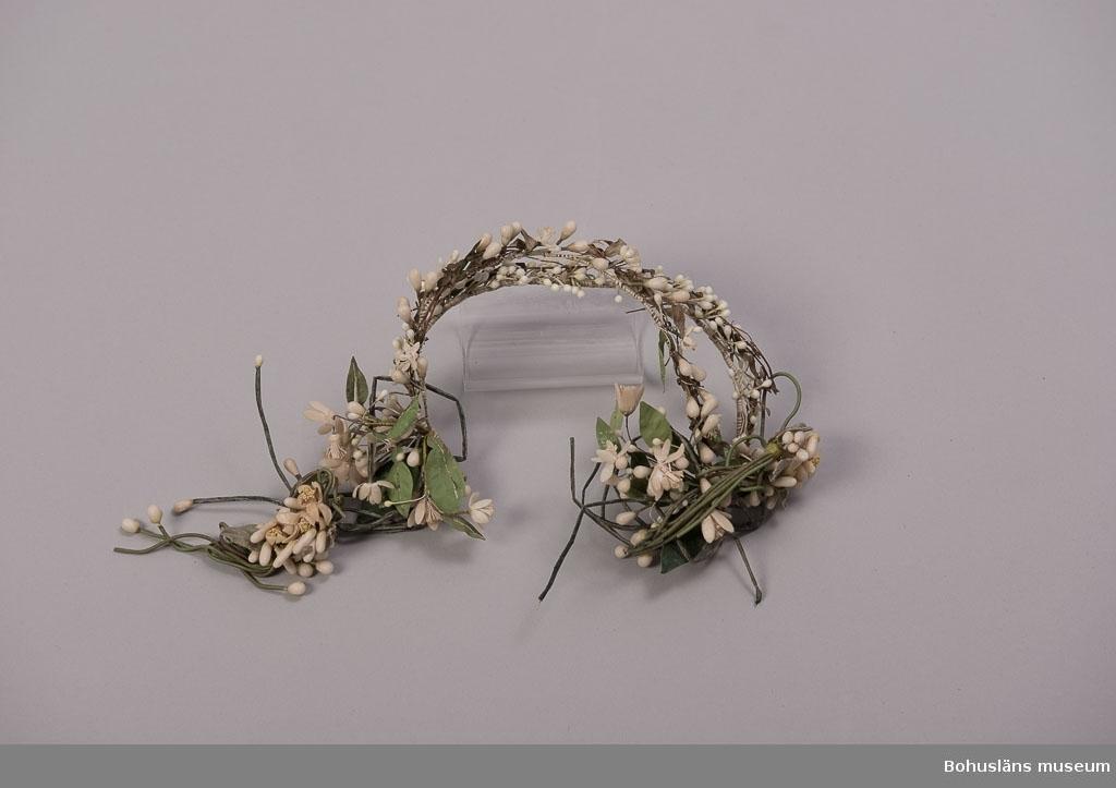 Diadem av konstgjorda blommor har tillhört Greta Karlssons brudutstyrsel från bröllopsdagen 30/12 1922. Sammanhör med UM018591 Brudslöja, UM18551 Skor och UM18595 Brudbukett.   Se UM018527