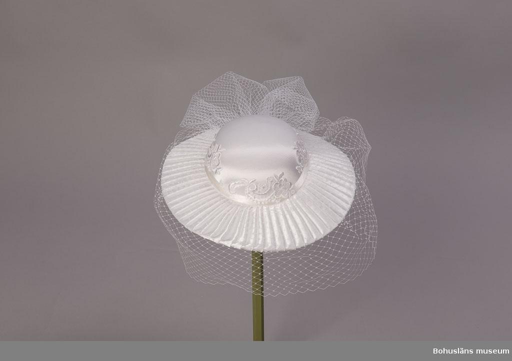 """Denna typ av hatt var på modet under första delen av 1990-talet och användes gärna vid tillfällen som cocktailpartyn, elegantare mottagningar och dylikt, kanske då ofta i en mer crémefärgad ljus nyans eller annan färg. Ännu vid förvärvstillfället modern och mycket efterfrågad. Denna vita variant utan någon färgbrytning mycket populär som huvudbonad i brudklädsel ända sen modellen lanserades. Bärs då till brudklänning i samma vita nyans. Slät glansig kulle med maskinbroderat blommönster runt kanten. Brett, stelt brätte klätt med veckat tyg. På brättet runtom vitt flor. Lapp på insidan kullen :""""100% polyester. Made in Taiwan, R.O.6."""" Som alternativ till denna hattyp har även hårklädslar i vitt varit modernt till brudklänning. Om Strands Mode se UM025656"""