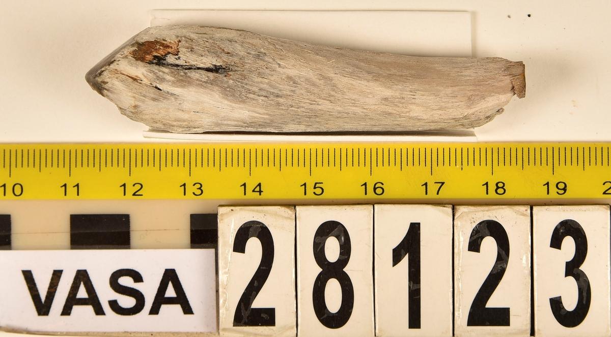 Fragment av horn. Avbruten i ena änden och sågad diagonalt till en spets i den andra änden. Ena sågytan har slipad sida. Hornets ursprungliga yta är bortnött och ytan känns närmast som torkat trä.