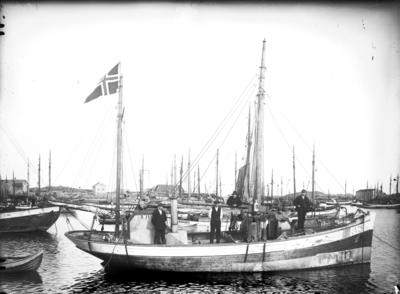 Eldre fiskebåt (fiskekutter) med mannskap om bord og et norskflagg til topps en akter mast.