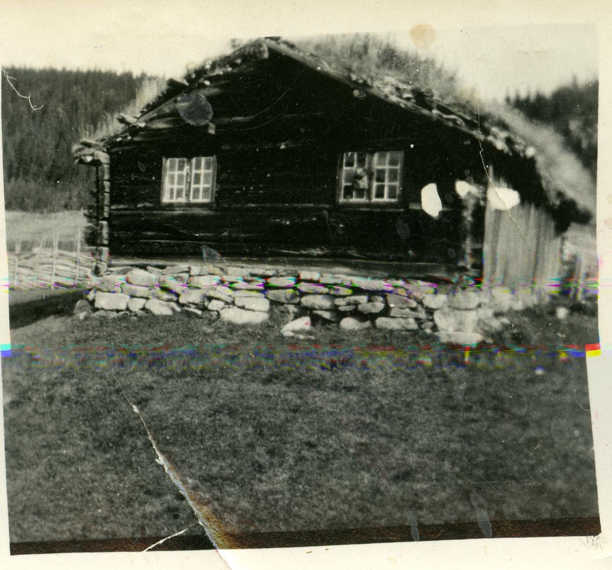 Tømmerstogo med steinmur og tørvtak.