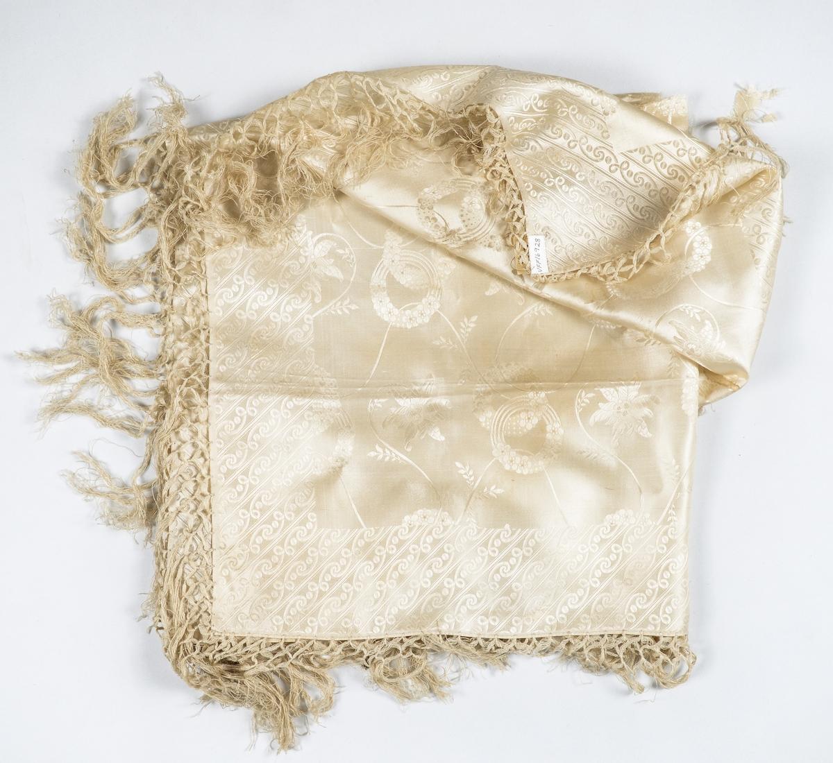 Tørkle i kremgul silkedamask. Påsette frynser langs kantane.