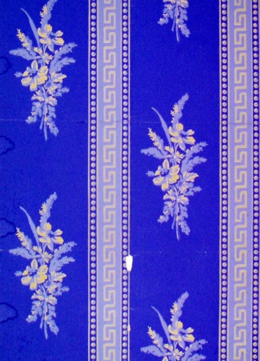 Lodrätta band dekorerade med meanderslingor och pärlstavar omväxlande med partier med blombuketter. Tryck i kobolt och ljusblått på ofärgat papper.
