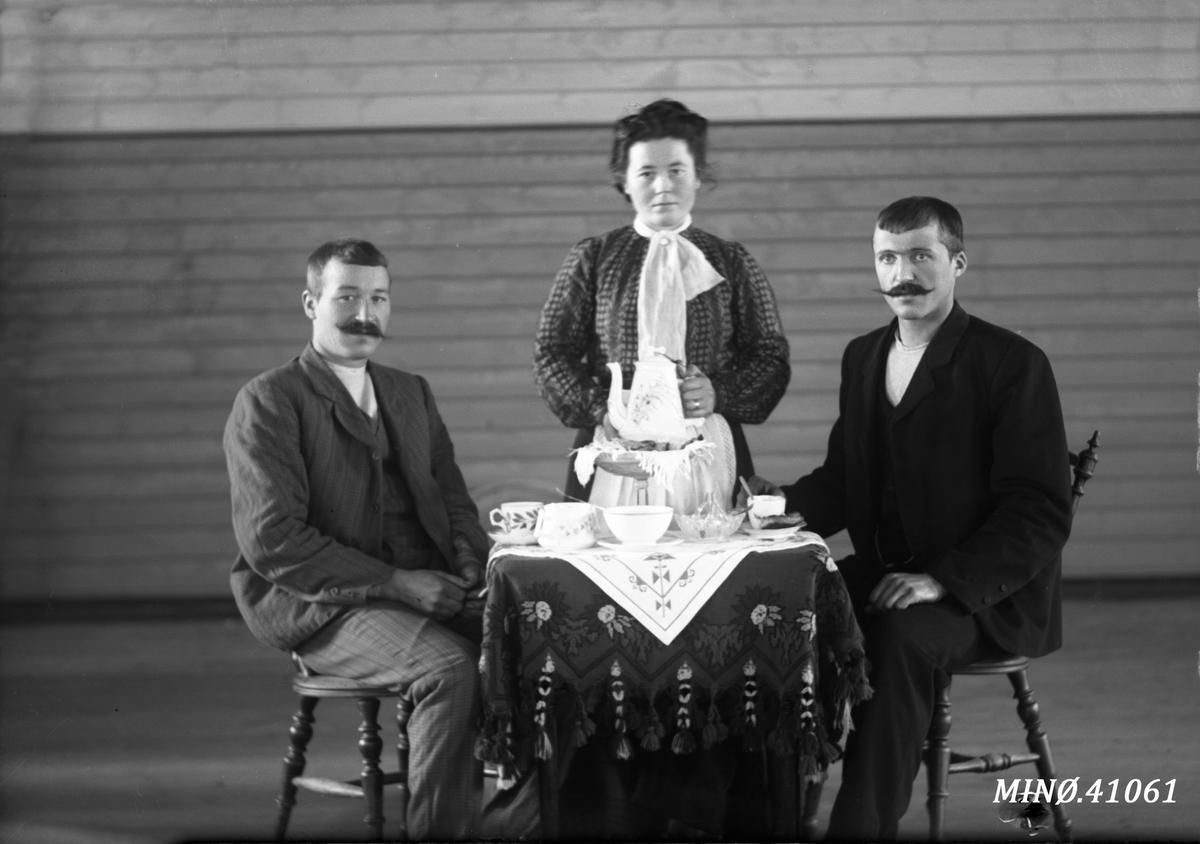 Portrett av to menn og ei kvinne som servere kaffe. Ole Aasgård