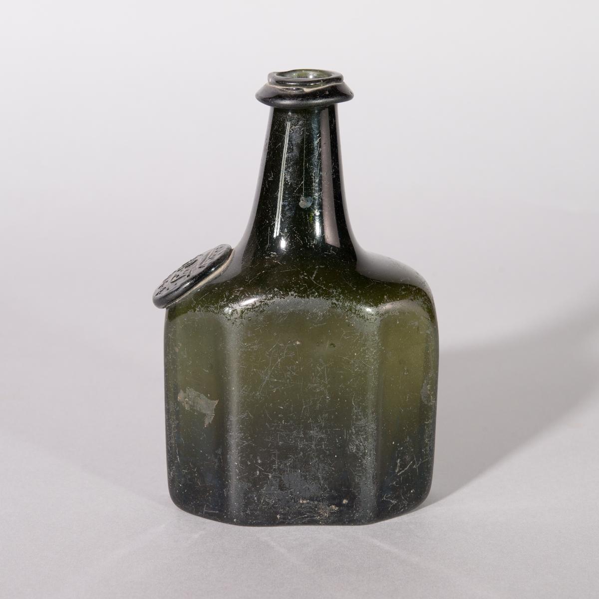 Flaska av grönt glas. 8-kantig kropp, axlar och rund hals. Sigill.