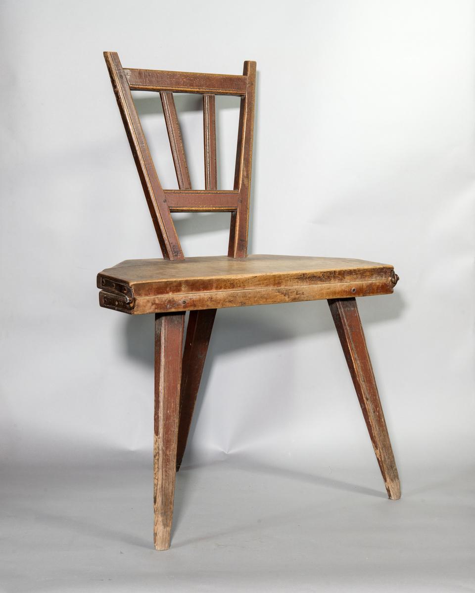 Bordsstol av trä, fällbar. 8-kantig sits i nedfällt läge. Rygg med tvärband och spjälor. Tre intappade ben och ryggen fungerar som fjärde ben i nedfällt läge. Gångjärn av järn. Rester av rödbrun och gul färg.