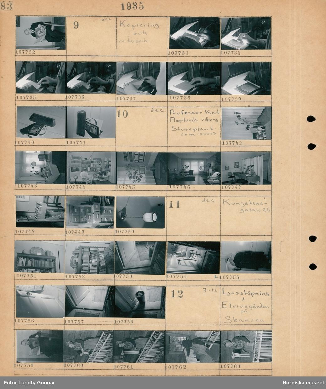 """Motiv: (ingen anteckning) ; En man sitte på en stol och läser tidningen Frihet.  Motiv: Kopoering och retusch; En person utför retusch på ett storformatsnegativ, en person visar hur man kontaktkopierar, tidningen """"Konsumentbladet"""" i ett brevinkast.  Motiv: Professor Karl Asplunds våning Stureplan 6 tom 07747; Interiör av en lägenhet med säng - fåtöljer - bord - bokhyllor - golvlampa  och soffbord, en lådhurts med fotografiskt material troligen på fotograf Gunnar Lundhs kontor, en taklampa.  Motiv: Kungstensgatan 26; En bokylla med böcker, interiör med trasmattor och en stol, en hall med hatthylla och ytterkläder, en papperskorg.  Motiv: Ljusstöpning i Elvrosgården på Skansen; En kvinna i folkdräkt stöper ljus."""