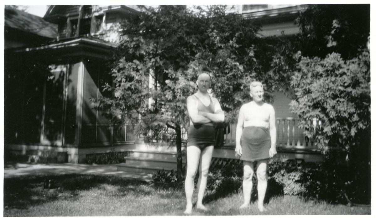 To menn avbildet i badetøy utenfor et hus. Bildet er tatt i Amerika.
