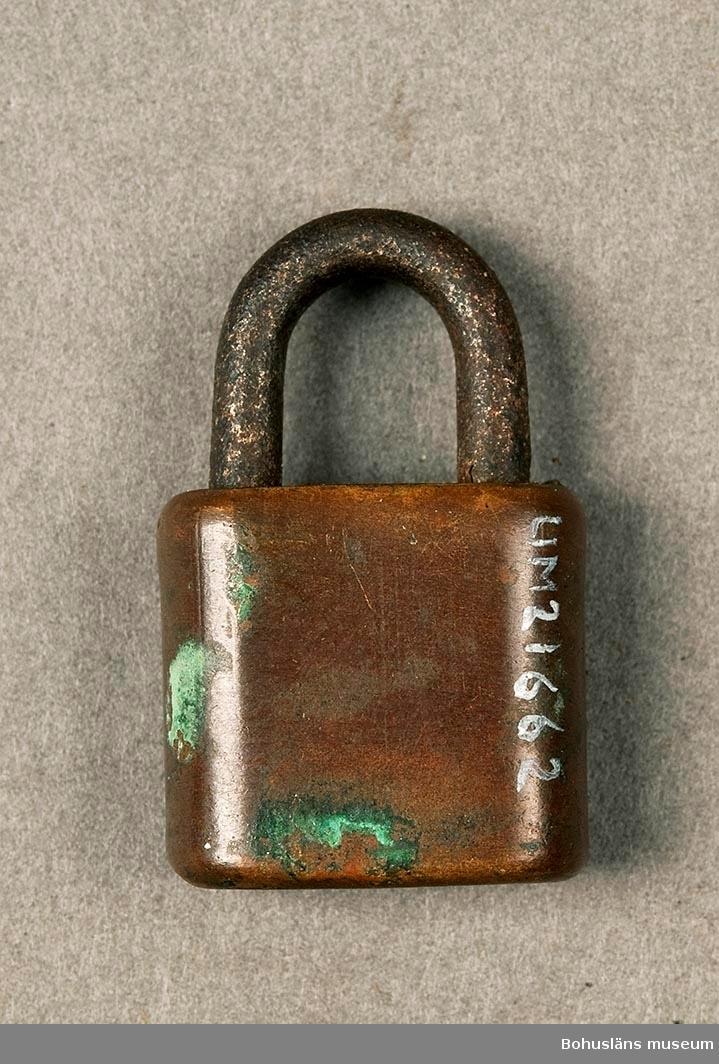 """Nyckel saknas. Märkt: """"Genuine Brass rustpoof. Made in USA"""". Mässinglås med järnbygel."""