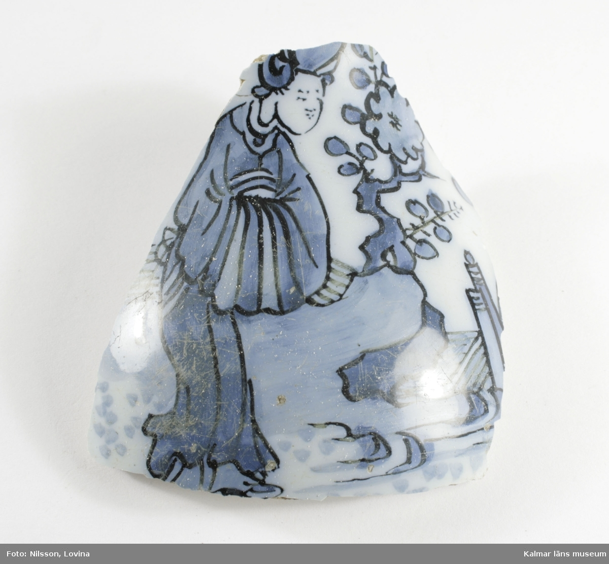 KLM 25037. Keramikfragment. Keramikfragment av gult gods som har vit glasyr invändigt och blå dekor utvändigt. Dekoren är ett kinesiskt sagomotiv: en kvinnofigur (geisha), ett träd med en stor blomma och delar av en borg.