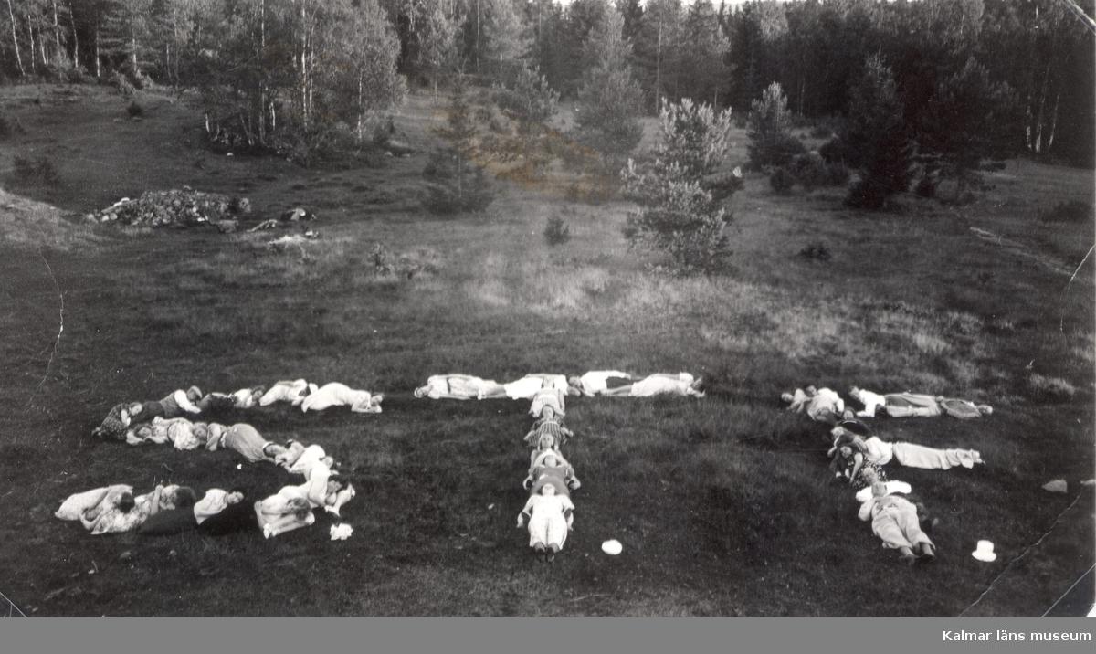 Amatörfoto av ett antal människor, som ligger utsträckta på marken tillsammans bildande bokstäverna STF.