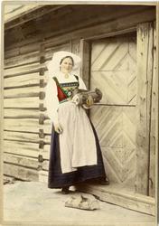 Kolorert fotografi av kvinne med drakt, bærer ved står foran