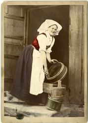 Kolorert fotografi av kvinne med drakt i døråpning med tre t