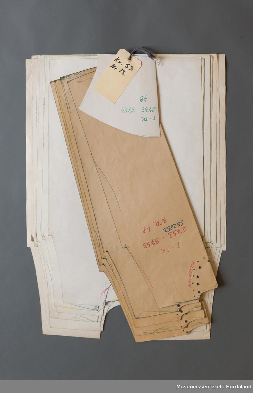Mønsterskantar i papp, brukt til å skjere ut ulike delar av plagg i klesproduksjon. Desse er til ein over- og underdel i kvalitet 53, nr. 13.