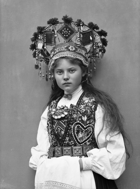 Studiofotografi av kvinne med brudedrakt og brudekrone. Stående med klede over hendene. 1899.