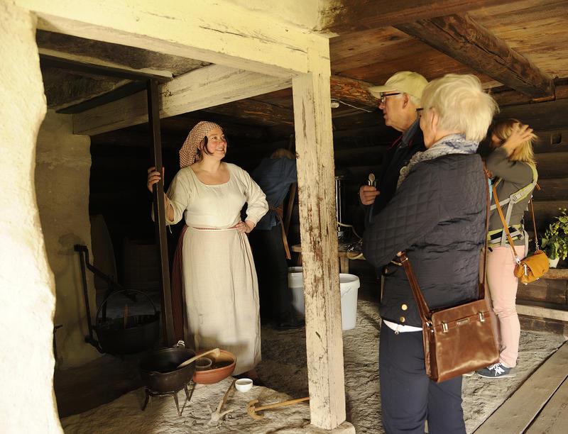 Kvinne med skaut og forkle over stakken lener seg på kanten av en peis hvor det henger ei gryte med grøt, kvinna snakker med to eldre mennesker som besøker museet. (Foto/Photo)