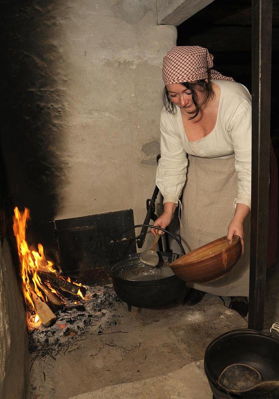 Jente med hvit trøye, rødrutete skaut og grått grovforkle står ved ilden på grua og øser vassgraut fra svart jerngryte over i rundt trefat.