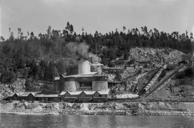 Svart-hvitt bilde av kalkbrenneri sett fra Mjøsa: store, runde kalkovner med tak og kalkbrudd i bakgrunnen.. Foto/Photo