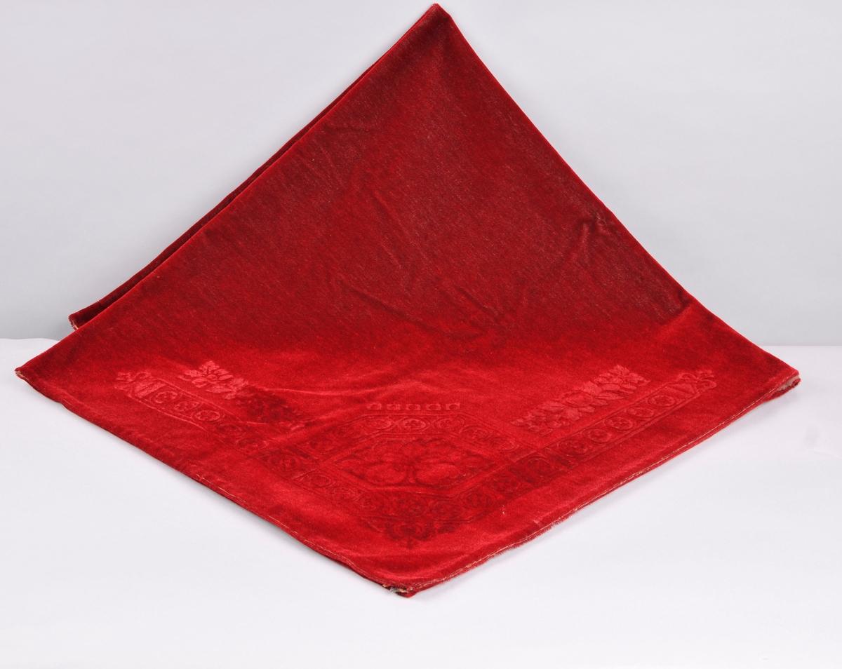 Fløyelsduk med prega mønster langs kanten og i kvart hjørne.