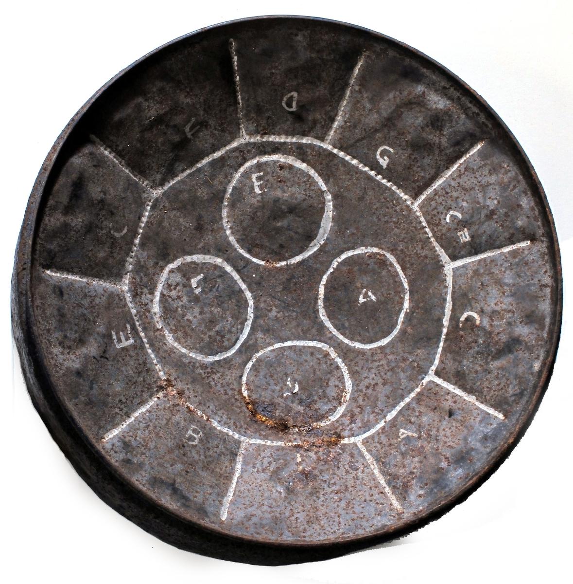Tromme  av jernblikk, toppen av et oljefat, malt dypblå på siden. Markeringer i hvitt i toppflaten.  Konkavt buet toppflate med en hvit ring, hvori 4 mindre ringer. Langs kanten feltinndelt med hvitt i riller i overflaten, feltene er av forskjellig størrelse. Ringer og felt er markert med  notebokstaver.  Lav blå side, uten bunn. Tynn snor til å henge over skulderen .  Musikkhistorisk museum, Ringve, har en make, men større, er toppen av et oljefat.