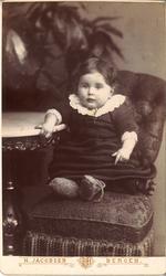 atelierfotografi av ei lita jente som sit på stol