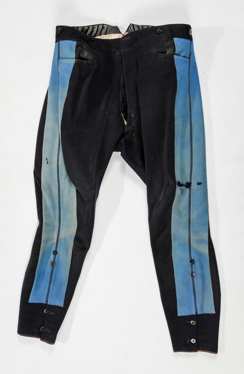 Uniformsbukse i svart kypertvove ulltøy, striper i blått klede i sidene. Høyrer til jakke nr. VFF 06703. (Står på arkivkort VFF 06706). Linning med svarte knappar til å feste bukseselane i. Ei lomme på kvar side. Gylf med knapping, hol nederst.  Spensel bak.
