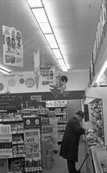 Interiør i kolonialbutikk. Kunder på jakt etter gode kjøp.