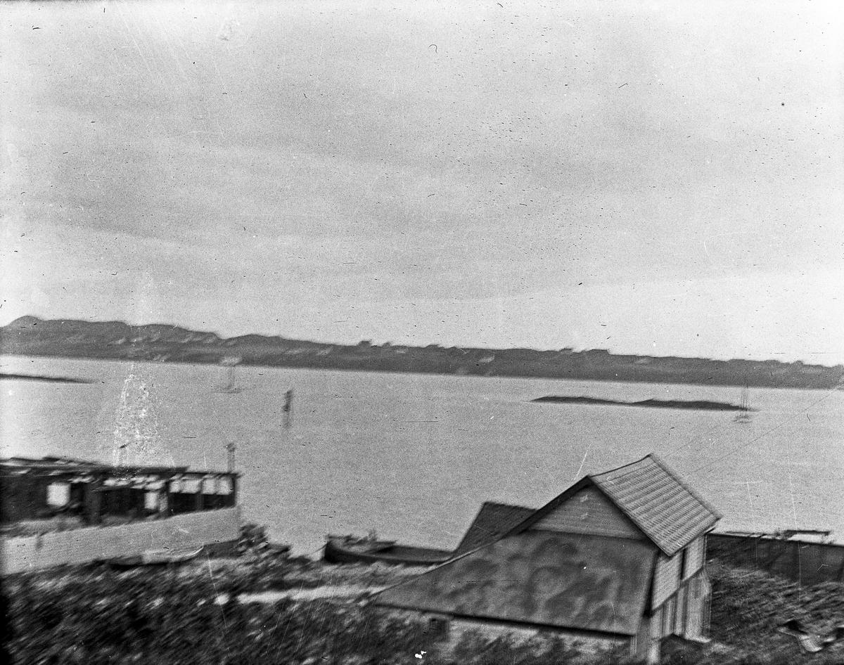 Kystlandskap. Bygninger og en båt i strandlinjen i forgrunnen. Hav med land i bakgrunnen.