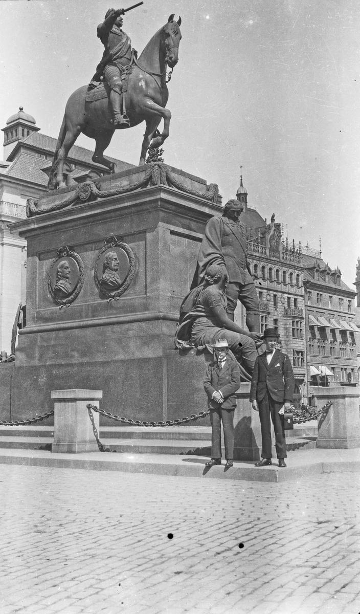 To menn som har stillt seg opp foran en stor statue av en mann til hest. Hverdagsfoto.