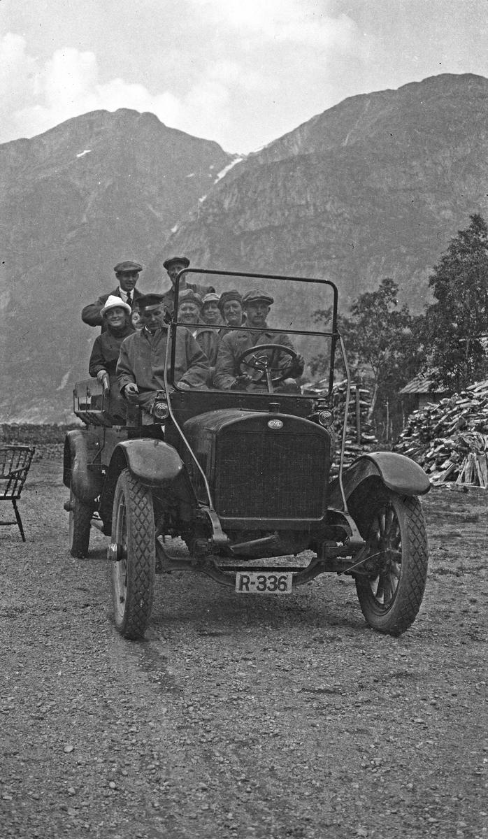 På biltur. Gruppebilde. Ni personer samlet i en åpen bil på tur i fjellet. Alle er godt kledd i frakk og hatt. Hverdagsfoto.
