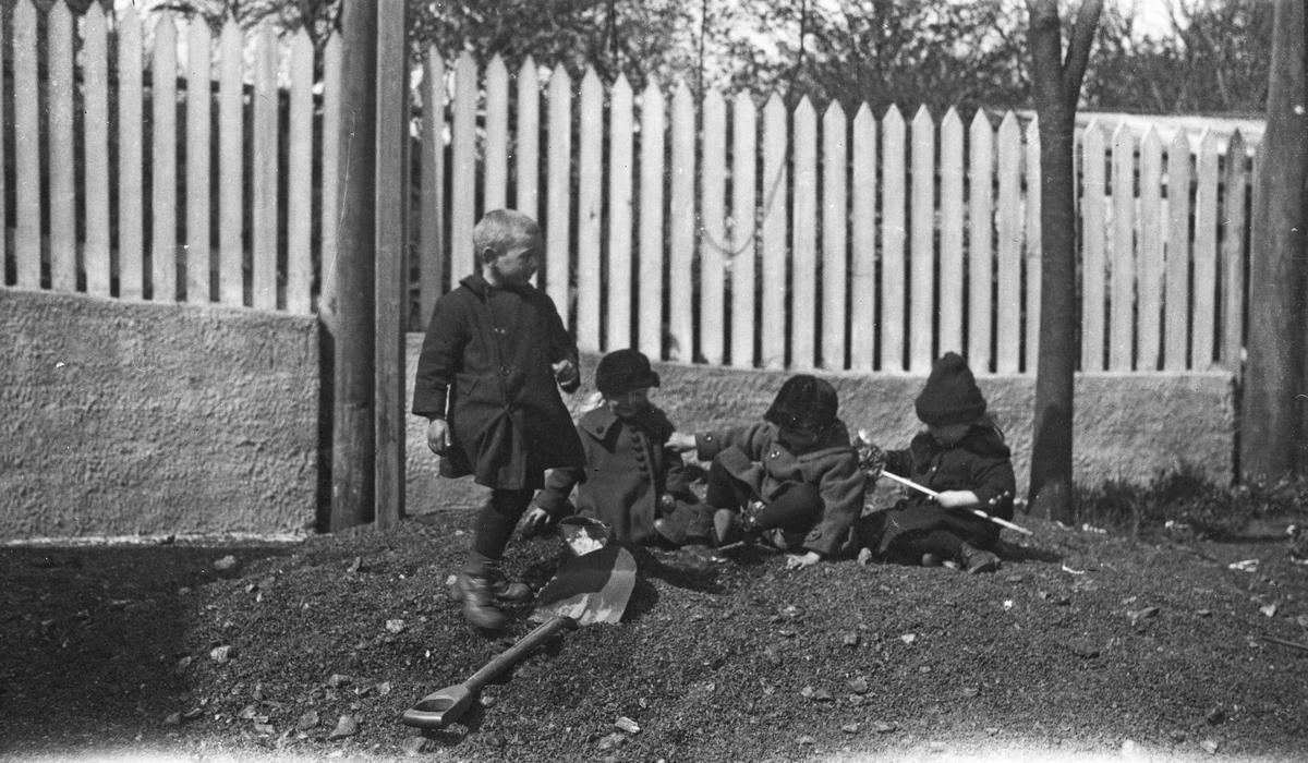 Sommer. Fire unger, to piker og to gutter leker i en jordhaug. Høyt stakittgjerde i bakgrunnen. Hverdagsfoto.