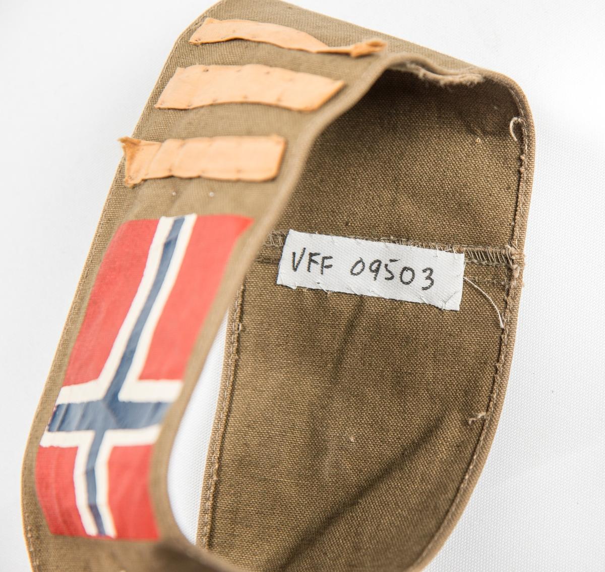 Armbind (Kaptein) i brunt bomullstøy. Påtrykt det norske flagget og påsydd tre tynne gule striper. Var sett på ermet til VFF 09539 Uniformsjakke (med knappenål).