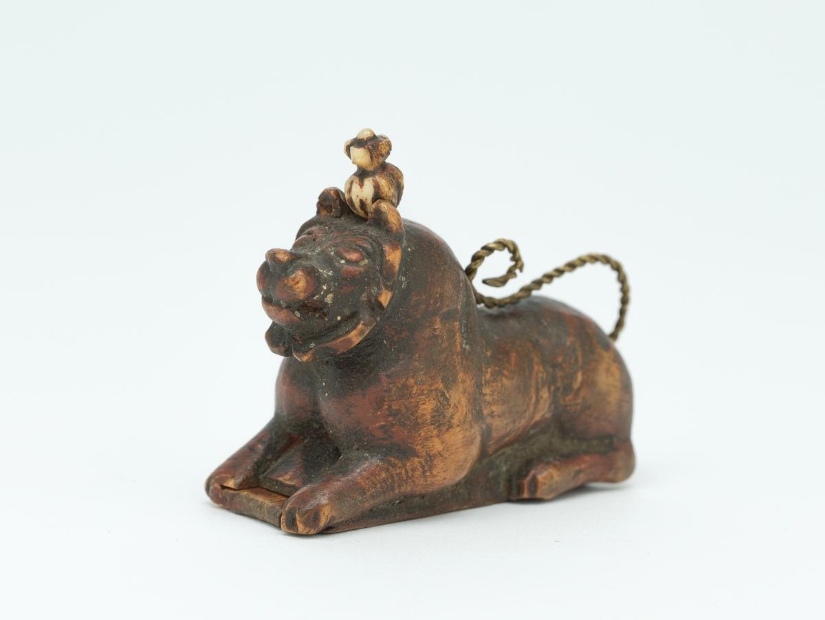 Liggende løvefigur av tre med snodd messingtrådshale. Lokk i bunnen.