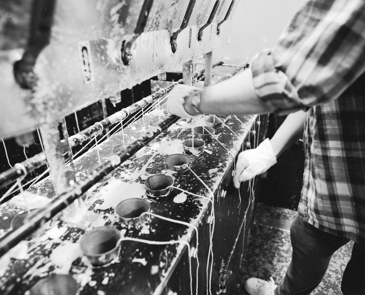 """Dokumentation av Liljeholmens stearinljustillverkning. Kyrkljus stöpmaskinerna, luftkylda (före 1970). Monica Hoffman drar upp och fixerar vekarna rätt, mitt i formen. Veken låses med """"persien"""" låsning."""
