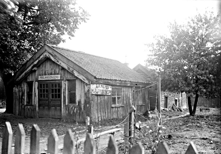 Bildtext: Skara. Kvarteret Tullen. Tomt 1 B. Söderströms, sedermera Jonssons Gördelmakeri, rivet hösten år 1927. Till höger ett uthus på samma tomt.