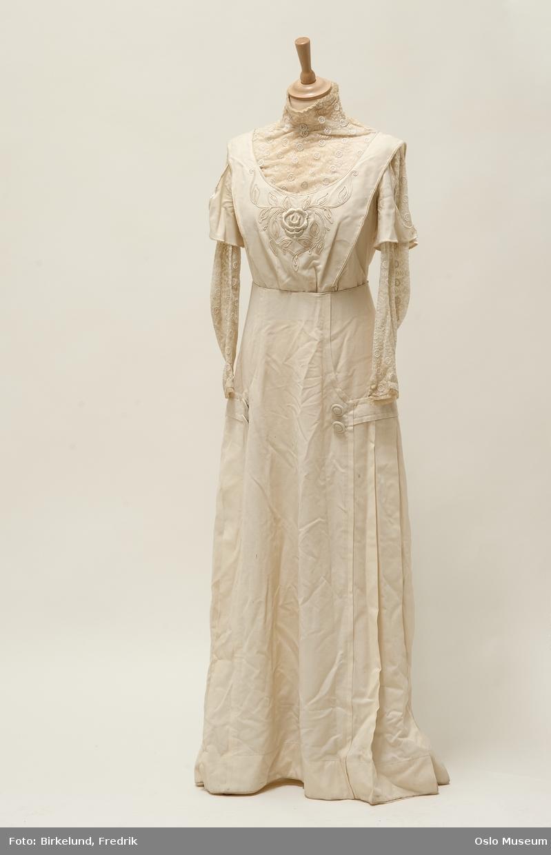 2d1f4a9b A: lang kjole i hvit tekstil. Blonde i ermer og halslinning. Brodert parti