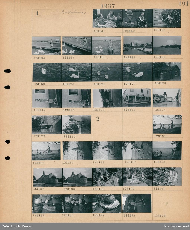 """Motiv: Östergötland, Vadstena; Porträtt av två kvinnor, porträtt av en man och en kvinna, porträtt av en kvinna, en kvinna på en brygga matar svanar, stadsvy med vatten, svanar på vattnet, porträtt av en kvinna framför ett hus, en kvinna framför en byggnad med skylt """"konsum"""", stadsvy med parkerade bilar, gatuvy med fotgängare.  Motiv: Östergötland, Vadstena ; En kvinna med cykel vid fiskenät, en kvinna med cykel vid strandkanten, exteriör av en byggnad, en kvinna sitter i en solstol och stickar, porträtt av tre kvinnor som dricker kaffe i en trädgård, porträtt av en man, porträtt av kvinna med en cykel."""