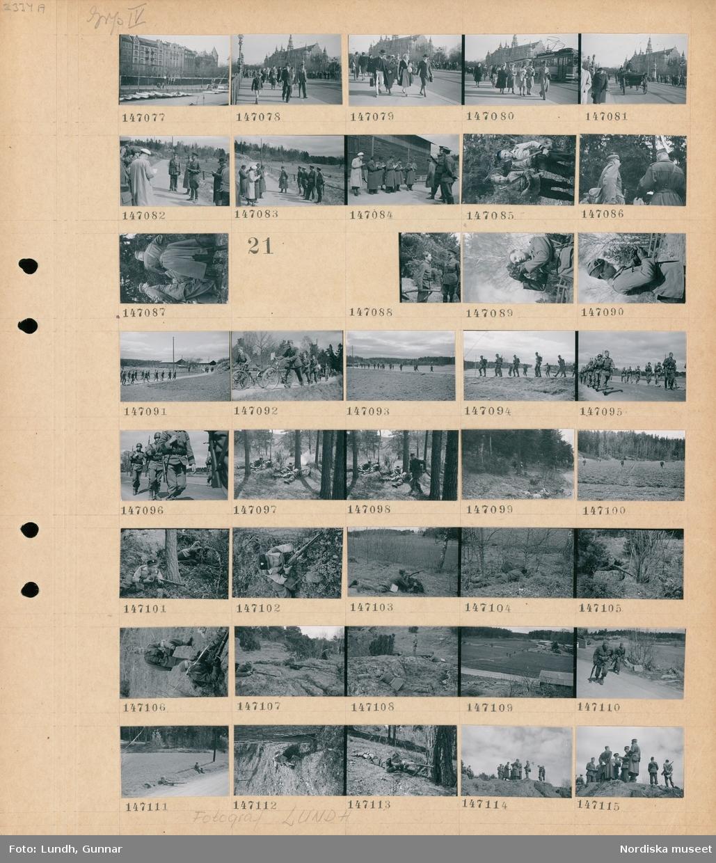 Motiv: (ingen anteckning) ; Stadsvy med vedstaplar på Strandvägen, fotgängare - spårvagn och hästdragen vagn på Djurgårdsbron, en grupp män som skriver i anteckningsblock troligen journalister står framför officerare i uniform, två pojkar med gevär.  Motiv: (ingen anteckning) ; En officerare står vid en soldat med gevär, en man i uniform med en filmkamera, landskapsvy med soldater som går på en väg, soldater leder cyklar, soldater med gevär ligger på marken i en skog, soldater springer över en åker, en pojke med gevär, en grupp officerare.