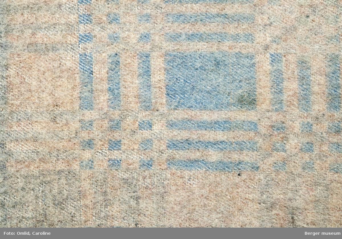 En prøve. Teppe med gjentagende mønster som blir brutt av samme mønsterbord i en annen farge.